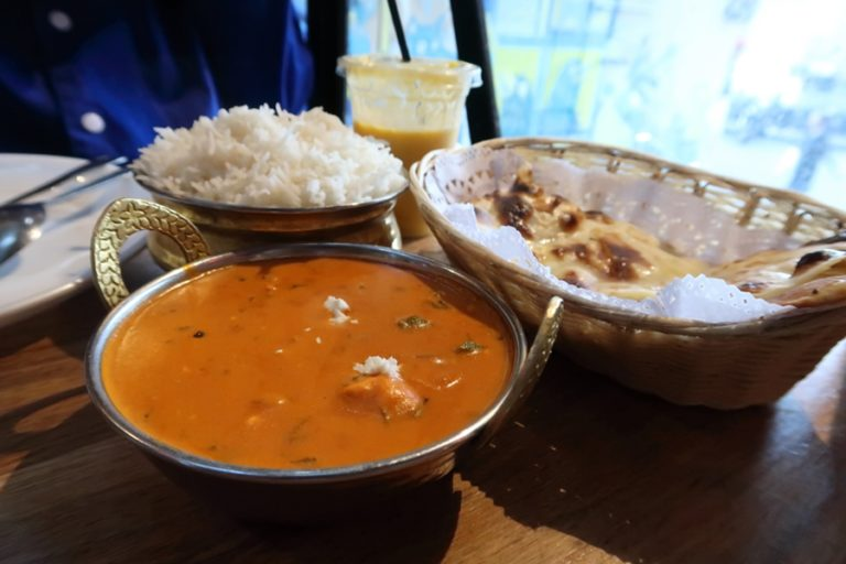 Butter chicken, mango lassi, naan bread and rice.