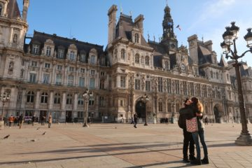 French couple kissing in front of Paris town hall