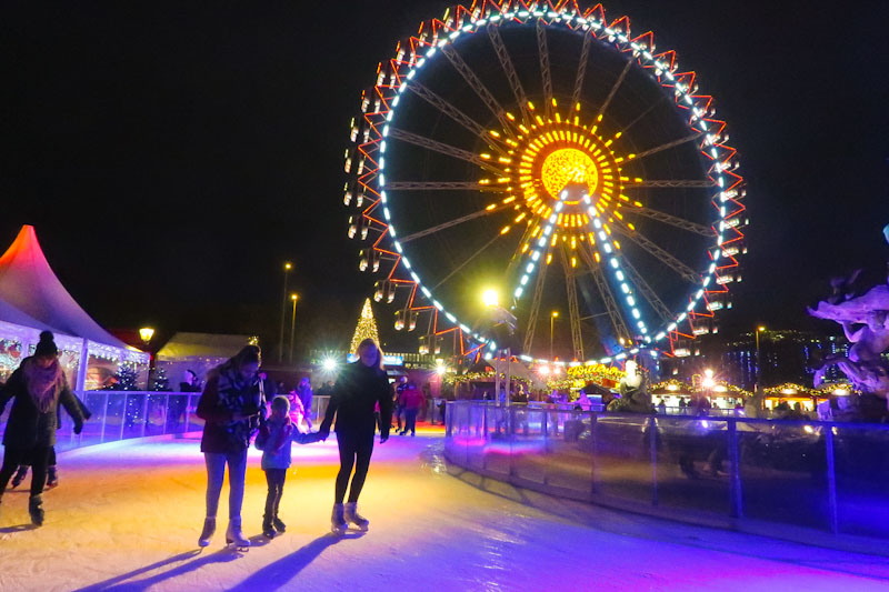 Ferris wheel at a Christmas Market in Berlin in winter at night with ice skating rink
