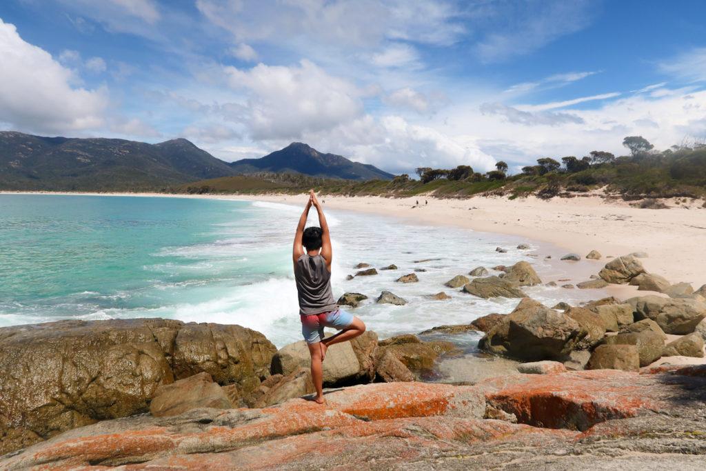 Yoga pose at orange rocks at wineglass bay tasmania