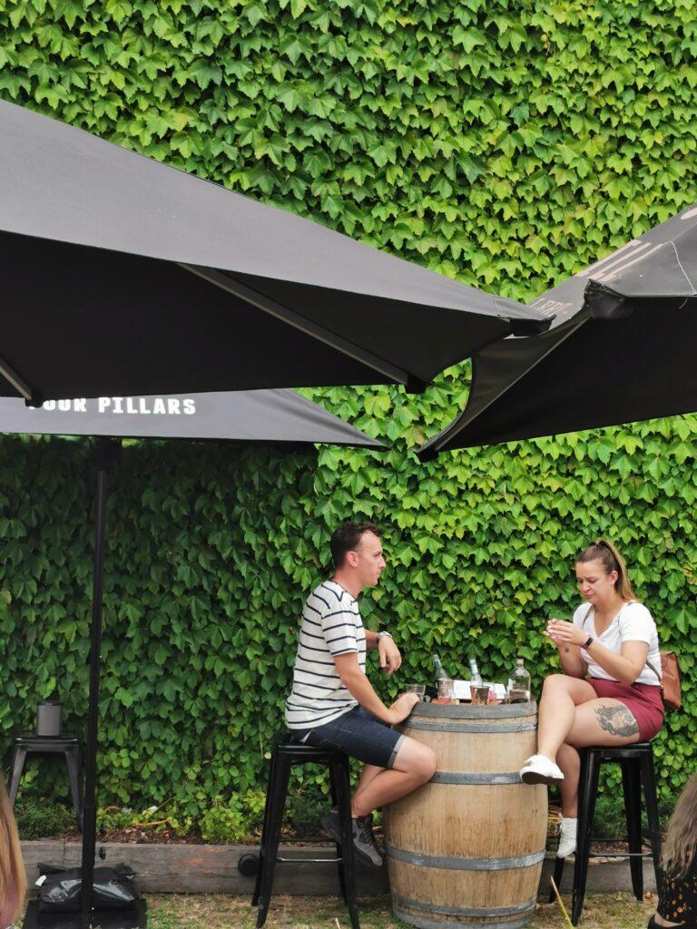 four pillar green umbrella couple gin distillery leaves
